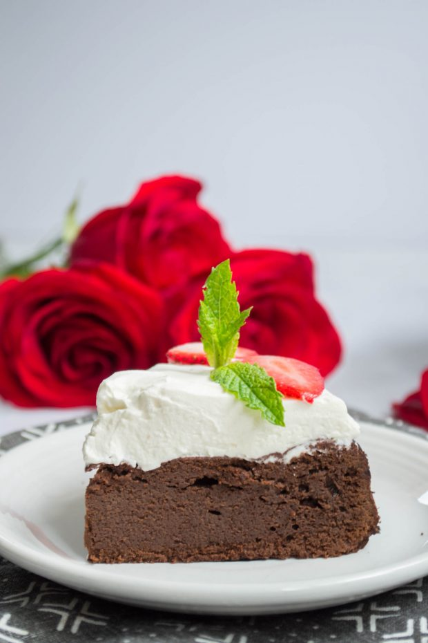 slice of keto flourless chocolate torte topped with whipped cream and garnished with mint leaves