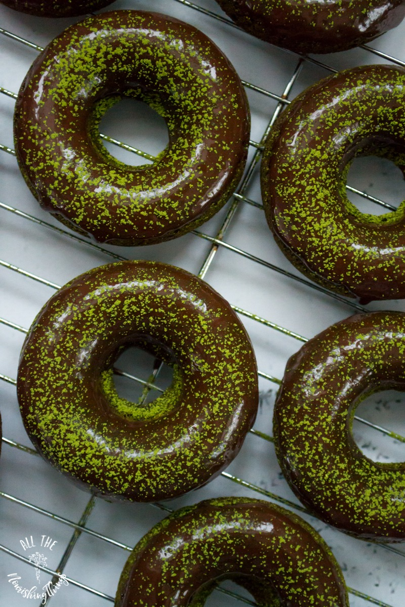 keto matcha-moringa baked donuts with green powder on top sitting on a cooling rack