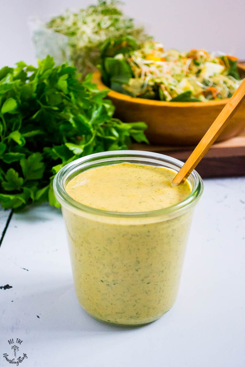 jar of avocado oil buffalo ranch dressing with salad and parsley in the background