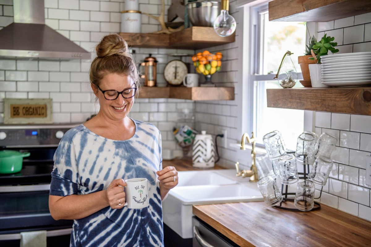woman in a blue tie-dyed shirt holding a mug of tea while standing in her kitchen
