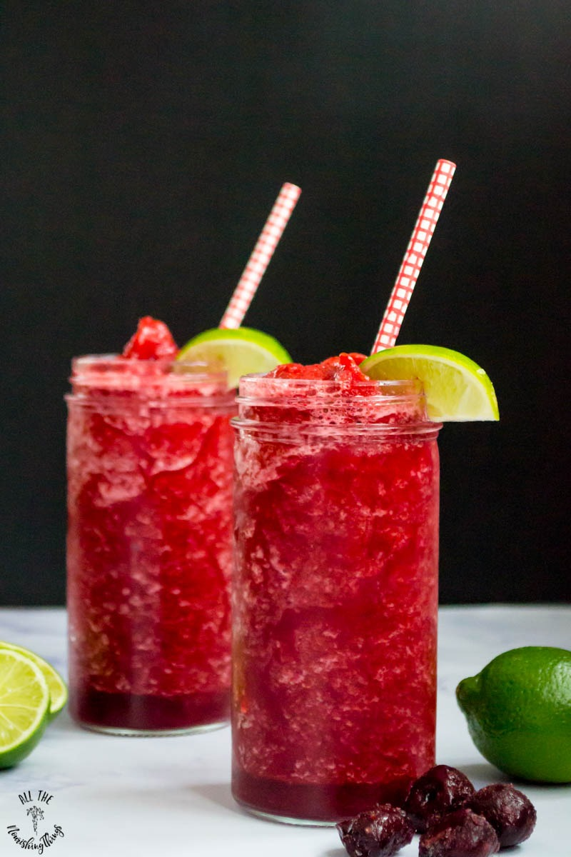 2 low-carb vegan cherry lime slushies garnished with lime wedges