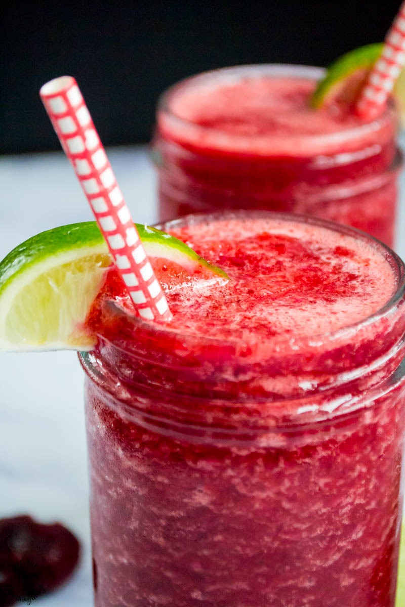 close up of cherry lime slushie with a red paper straw