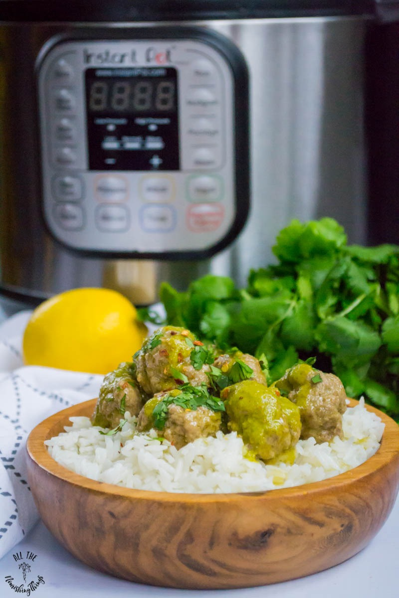 wooden bowl filled with rice and cilantro meatballs with instant pot, lemon, and cilantro in background