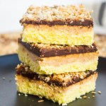 3 keto toasted coconut and chocolate bars stacked on black plates