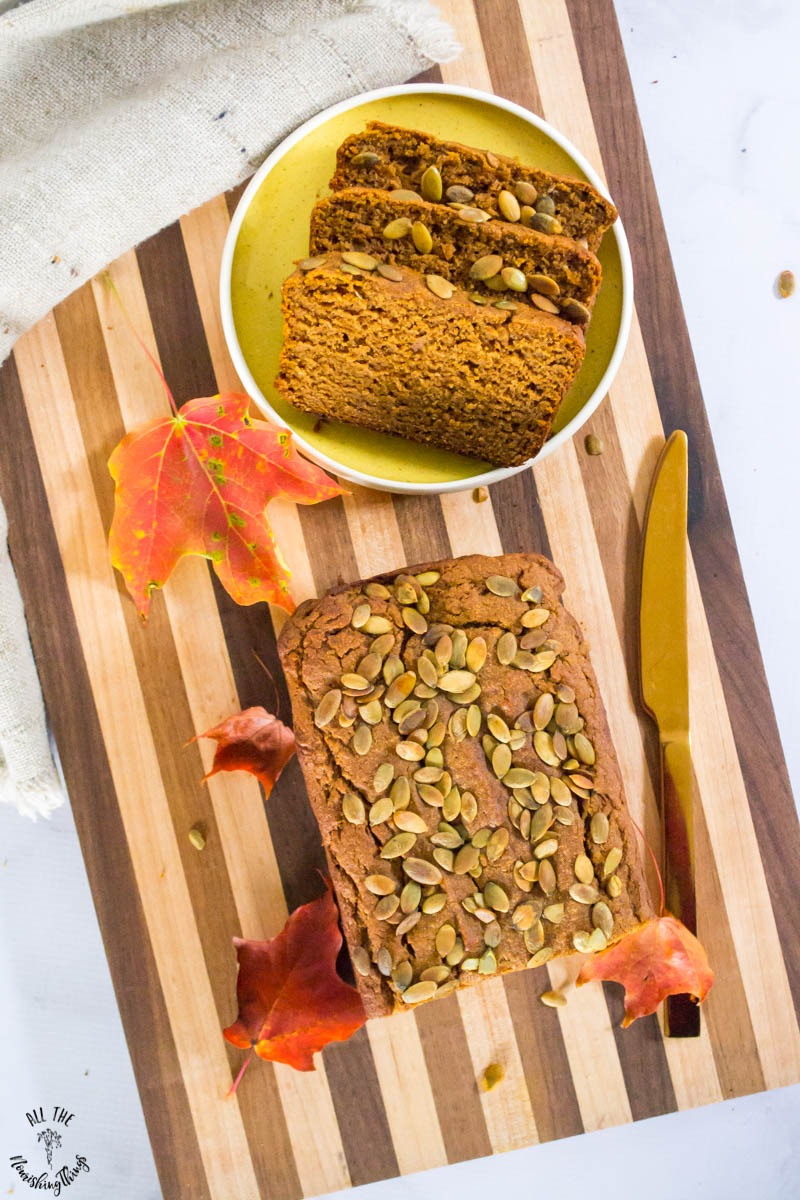 overhead view of best cassava flour pumpkin bread on a striped wooden cutting board