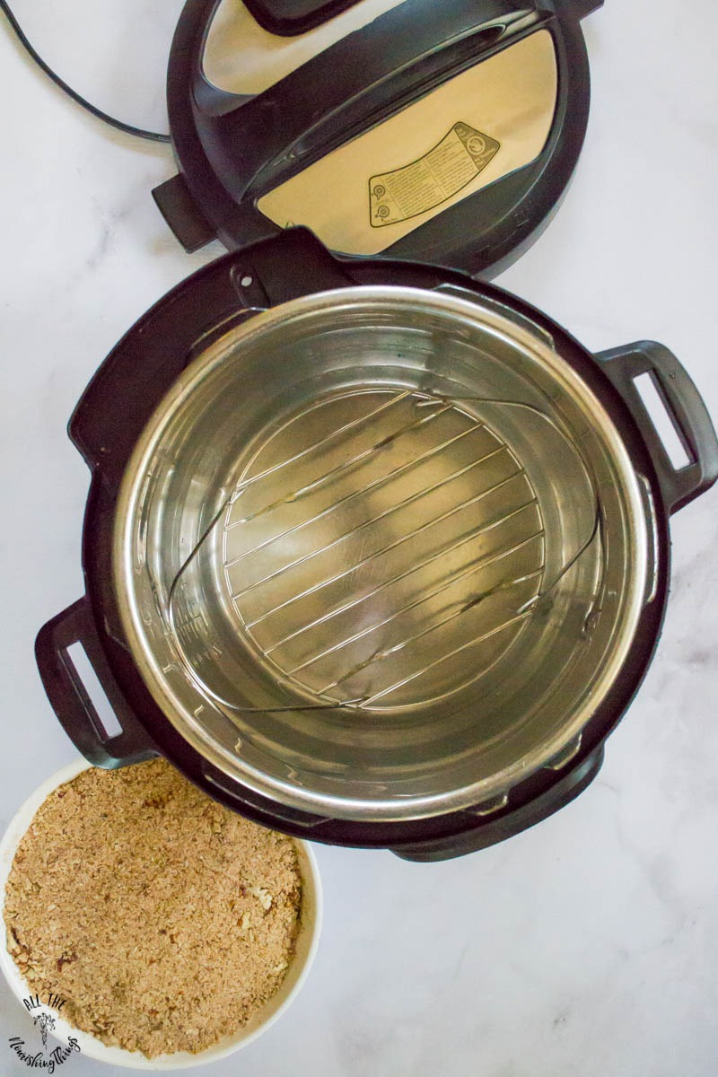 instant pot with metal trivet and a cup of water
