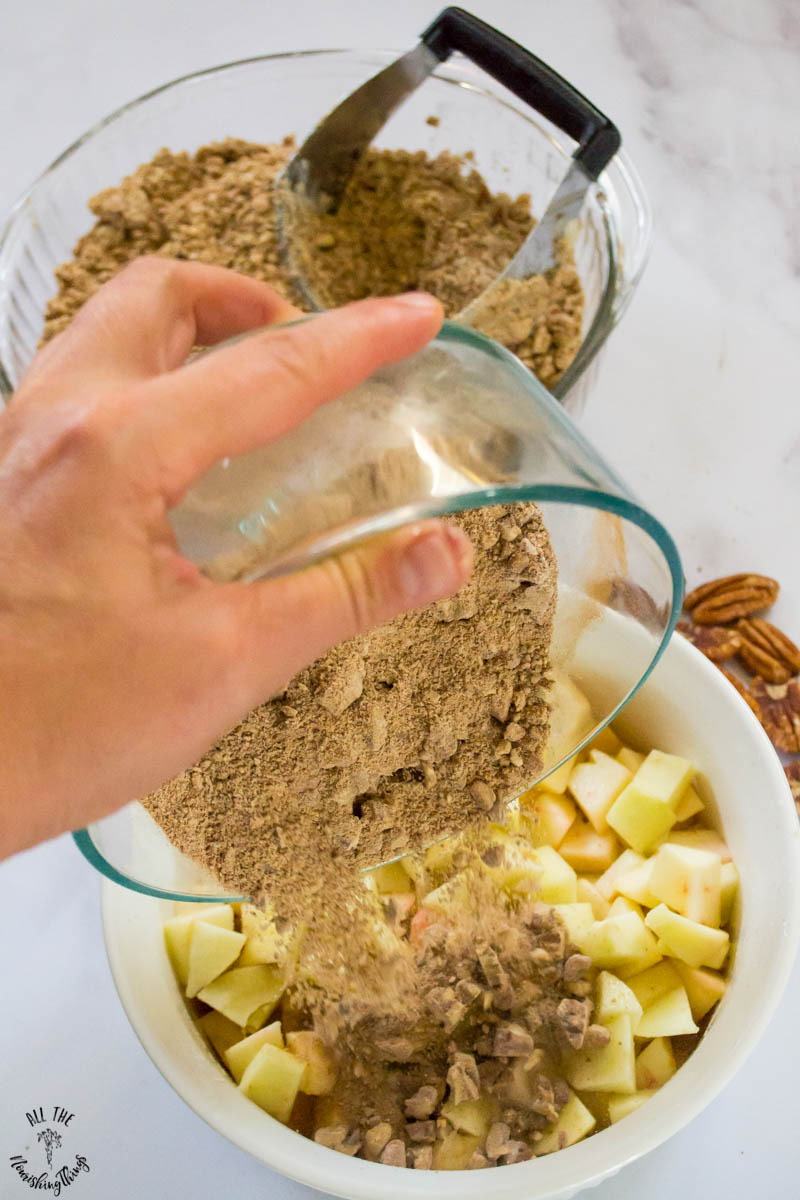 mixing together paleo instant pot apple crumble ingredients