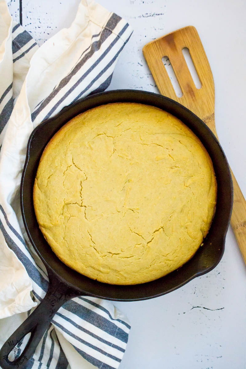 gluten-free southern cornbread in a cast iron skillet with a wooden spatula