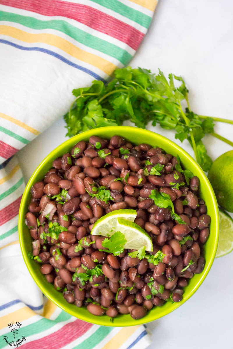 green bowl of instant pot cilantro lime black beans with colorful tea towel and fresh cilantro
