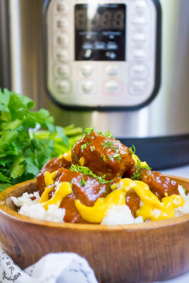 instant pot beef enchilada meatballs with chopped cilantro and a cheesy sauce served over white rice in a wooden bowl with instant pot in the background