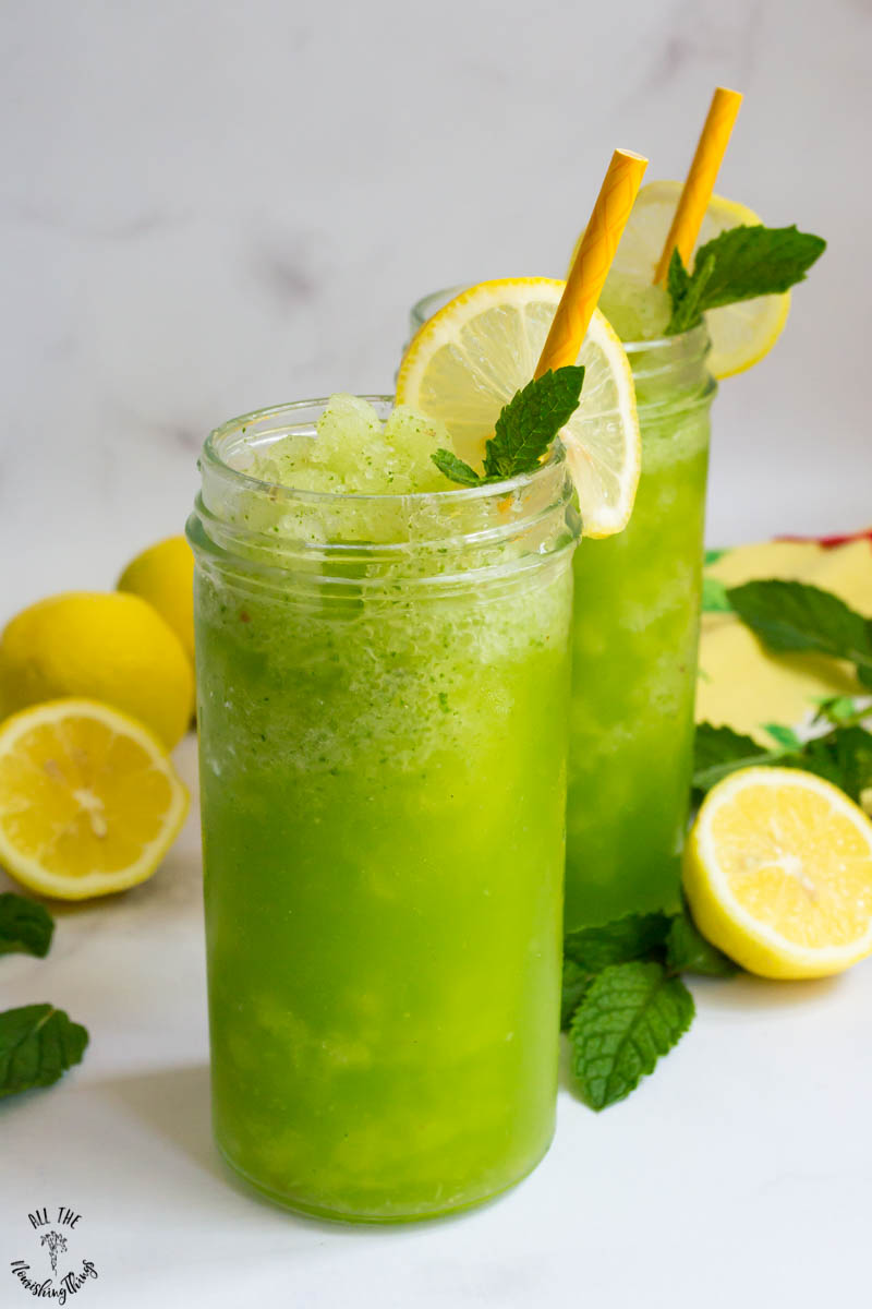 2 glasses of light green keto frozen mint lemonade with yellow paper straws and slices of lemon