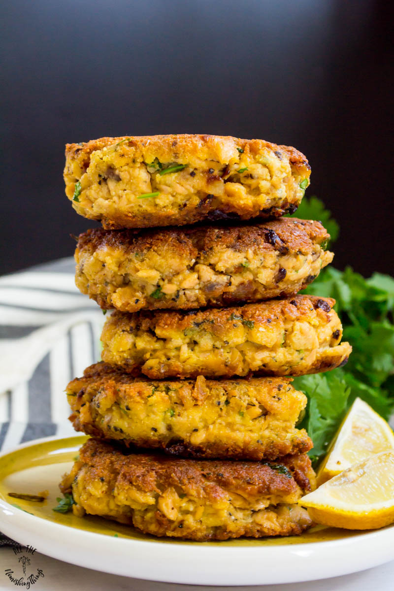 stack of keto salmon patties on a light green plate with 2 lemon wedges