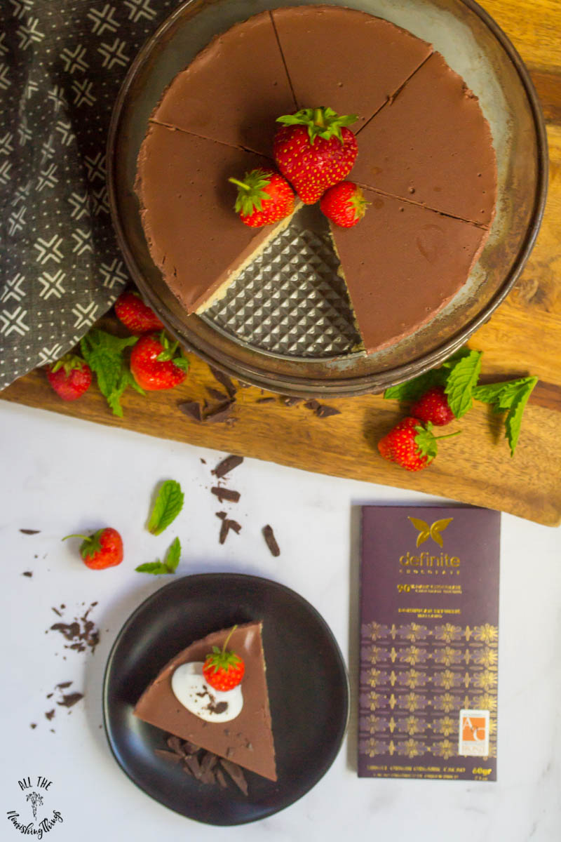 vegan no-bake chocolate pie garnished with fresh strawberries on a wooden cutting board with chunks of chocolate all around