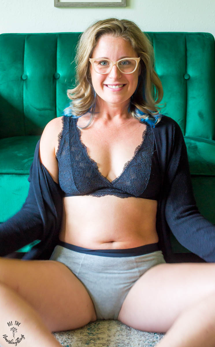 lindsey lockett wearing grey period underwear and a black bra with black cardigan and sitting on the floor in front of a green couch