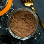 glass jar of instant keto hot chocolate mix with a gold spoon