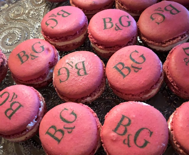 A plate of pink macarons imprinted with the letters B&G.
