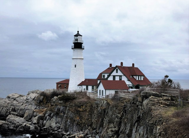 A white lighthouse and a cluster of red-roofed buildings sit on a rocky promontory with the ocean in the background.