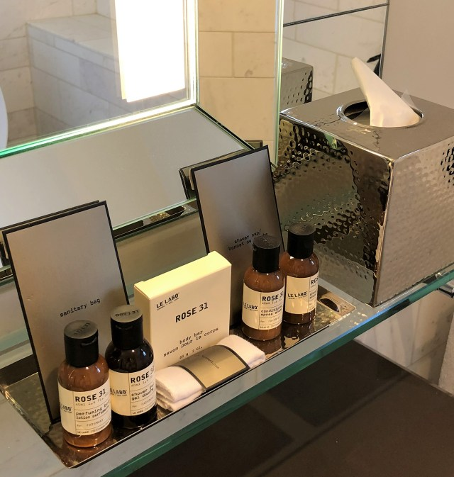 A row of toiletries by Le Labo Rose 31 on a vanity shelf next to a silver tissue holder