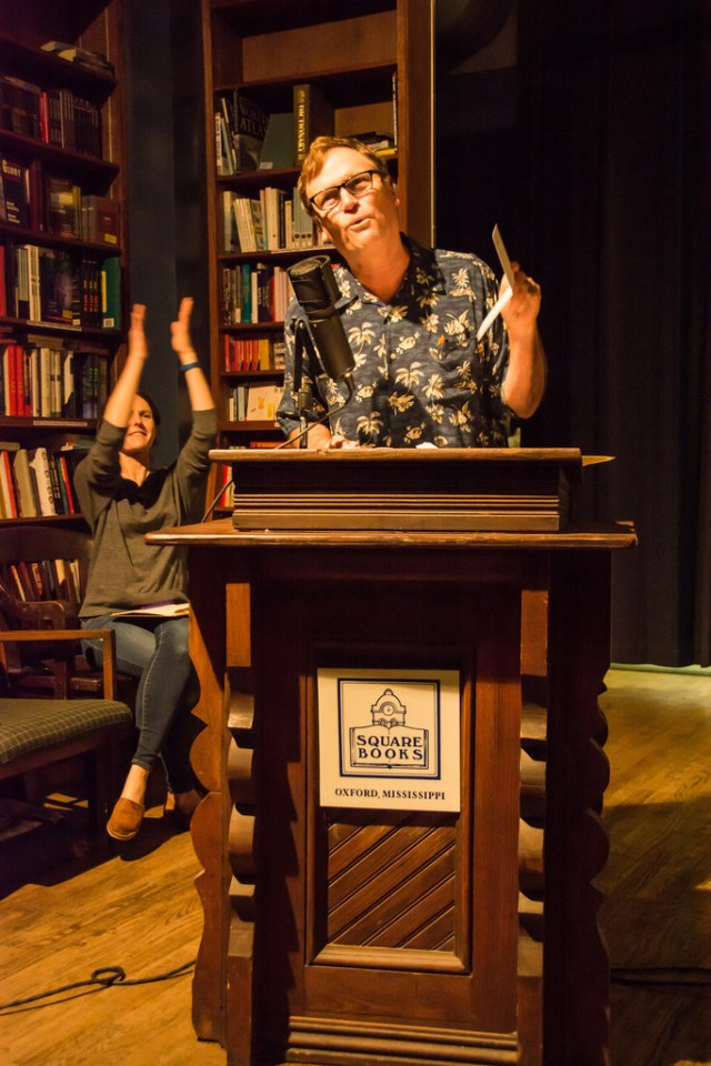 A man in a flowered shirt stands at a podium in a bookstore, a woman in the back claps her hands overhead