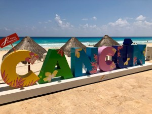 Large colorful letters spell out CANCUN, ocean in background
