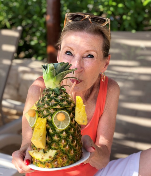 A woman (me) sipping from a straw inserted in the back of a pineapple, fruit pieces make a face on the front