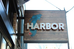 A wood outdoor sign reads: Harbor.