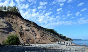 A large sand dune slopes down to a rocky beach with several people gathering