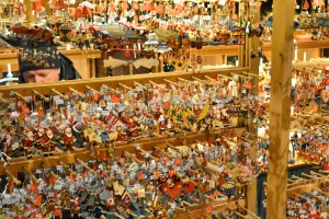 Four rows of Christmas tree ornaments on display in a store