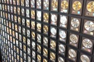 A wall of silver and gold record albums in black frames.