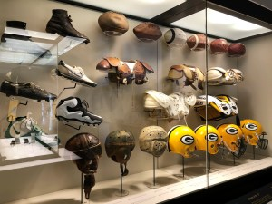 A display of vintage football helmets, shoulder pads, shoes and balls