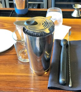A glass, tin cup with strainer, black napkin, muddler and bar spoon