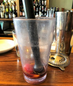 A tall clear plastic glass with a cherry, a bit of liquid and a muddler