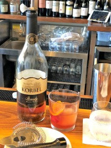 A bottle of Korbel brandy next to a short glass filled with brandy, ice and orange peel