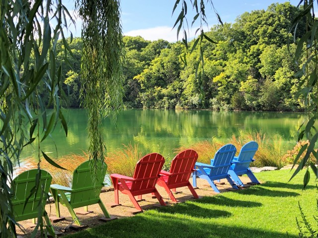 Six Adirondack chairs overlook a peaceful pond