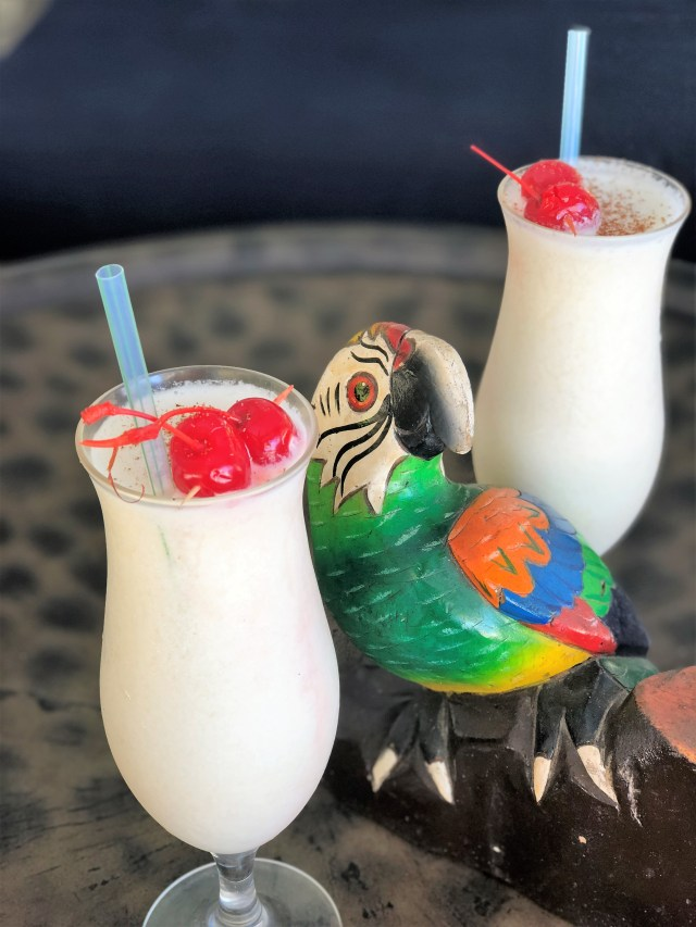 Two tall white drinks with cherries on top, separated by a parrot figurine