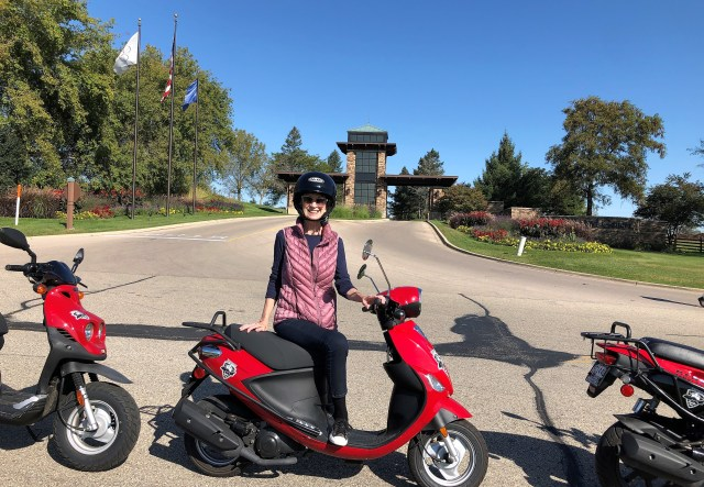 A woman (me) standing next to a red and black motor scooter by the side of a road