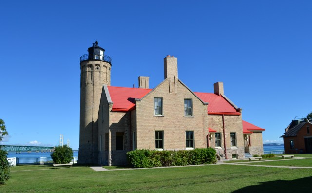 A two-story brick home with red roof and a lighthouse attached on the left.