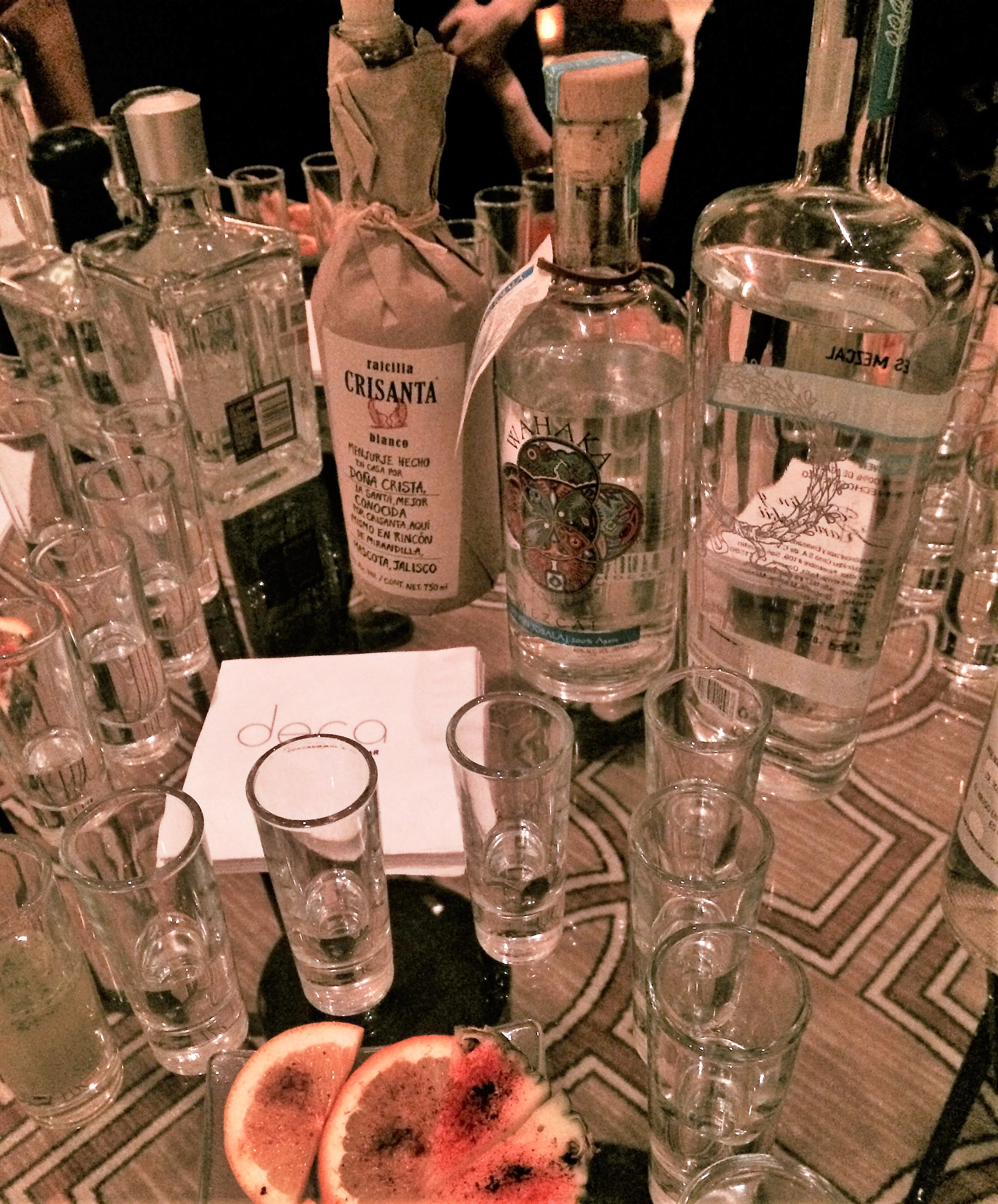 A tabletop assortment of tequila bottles, shot glasses and a plate of orange slices