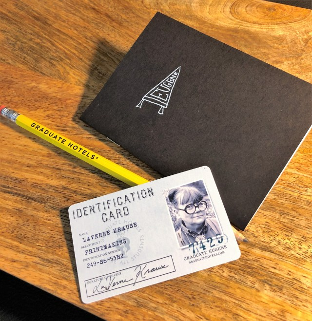 A student ID card, pencil and small notebook against a wood background