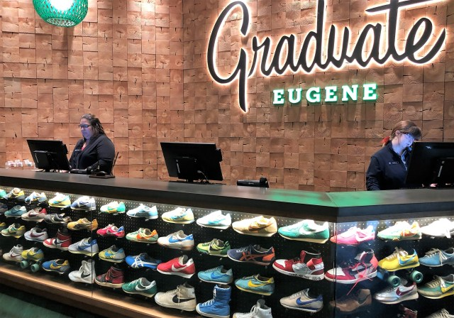 Two clerks stand behind a reception desk, which is circled on the bottom by a display case of dozens of colorful athletic shoes. The wall sign reads Graduate Eugene.
