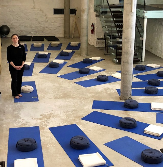 A yoga teacher dressed in black stands at the center of blue yoga mats arranged in a semi-circle.