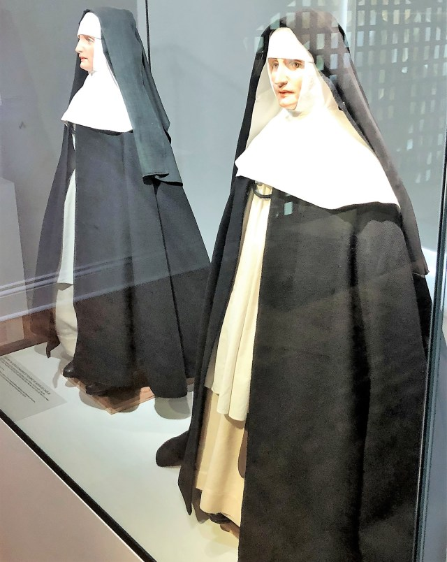 Two mannequins dressed like nuns in heavy black and white layers of clothing.