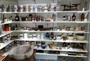 A wall of shelves displays old-time apothecary jars, mortars and pestles, and other pharmaceutical paraphernalia.