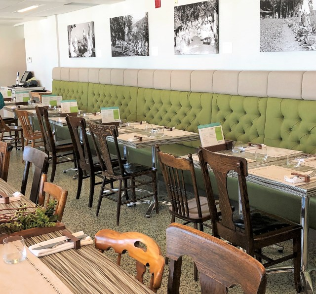 Restaurant with banquette seating along a green upholstered wall.