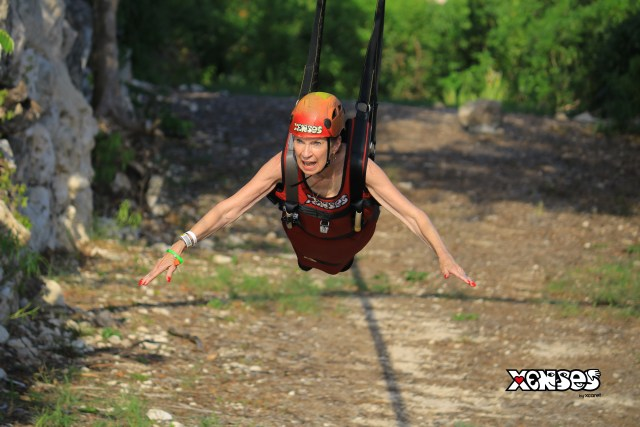 Front view of a woman, the author, with outstretched arms is strapped into a zipline, soaring like a bird. Her mouth and eyes are wide open.