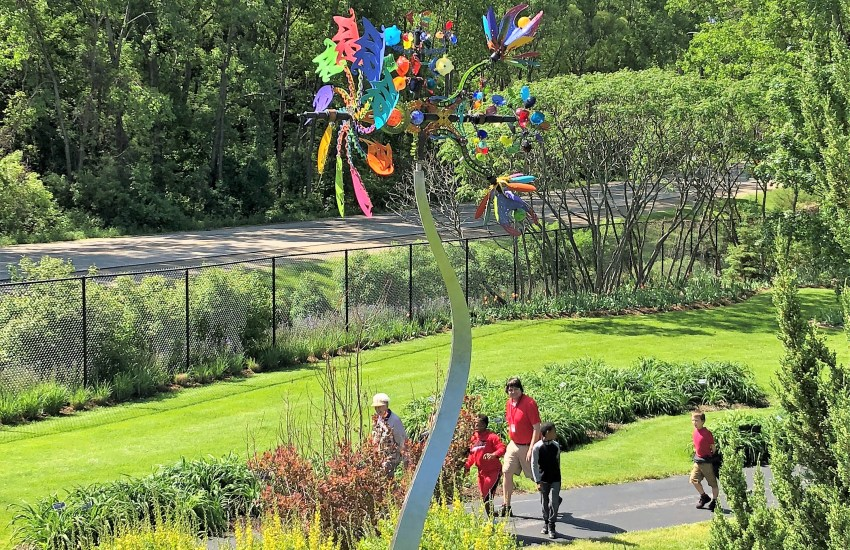 A contemporary sculpture similar to a weathervane emerges from a planted flora garden with woods and a path in the background