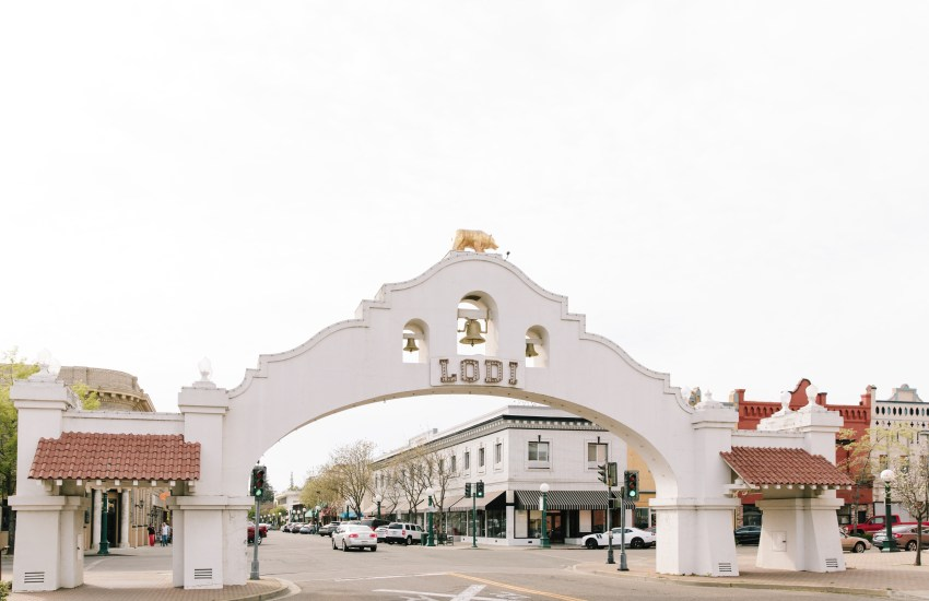 A white mission-style arch with letters spelling LODI crosses above a city street
