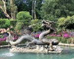 A fountain shaped like a dragon with water spewing from its mouth sits in a pool surrounded by flowers, shrubs and trees.