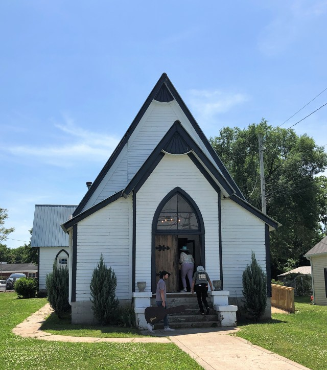 Street view of a small white church, 3 people are entering the front door
