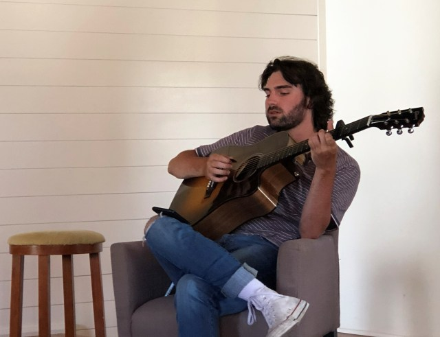 A seated songwriter Andrew Groom strums his guitar